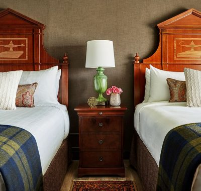 Two Queen Beds with a nightstand and green lamp