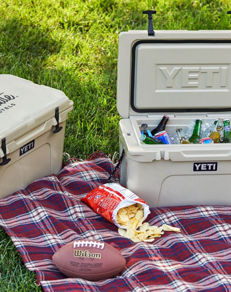 Yeti Cooler with a Football and Bag of Chips Next to it