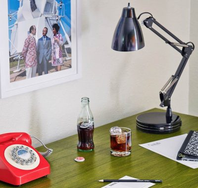 side table in guest room with a telephone and lamp