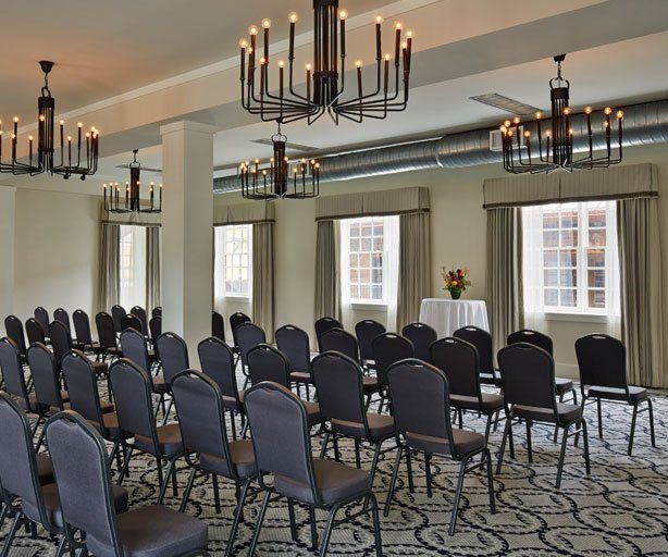 large meeting room with chairs and hanging chandeliers