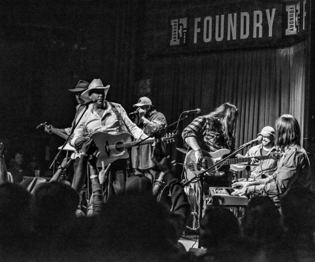 black and white photo of the kinchafoonee cowboys playing on the foundry stage
