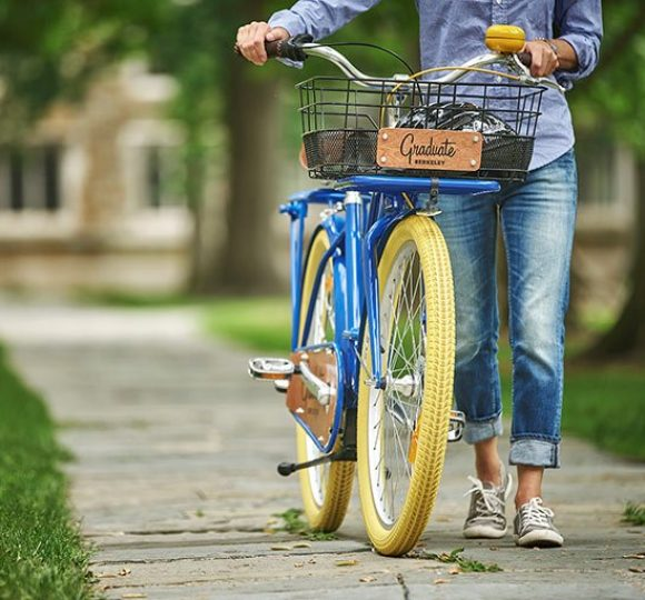 woman walking her graduate branded bicycle