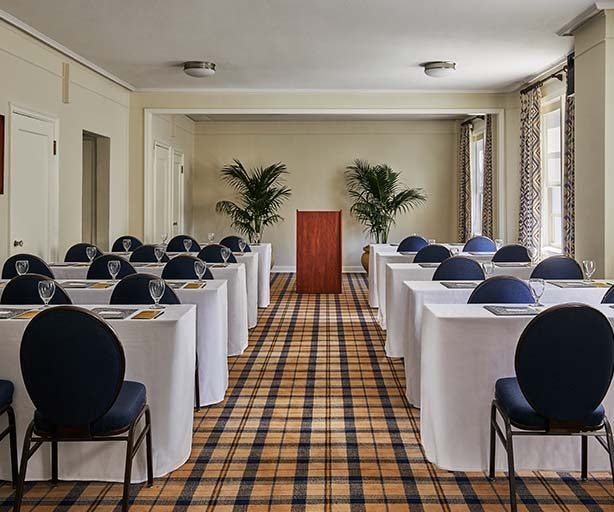 meeting room with multiple tables setup for a conference