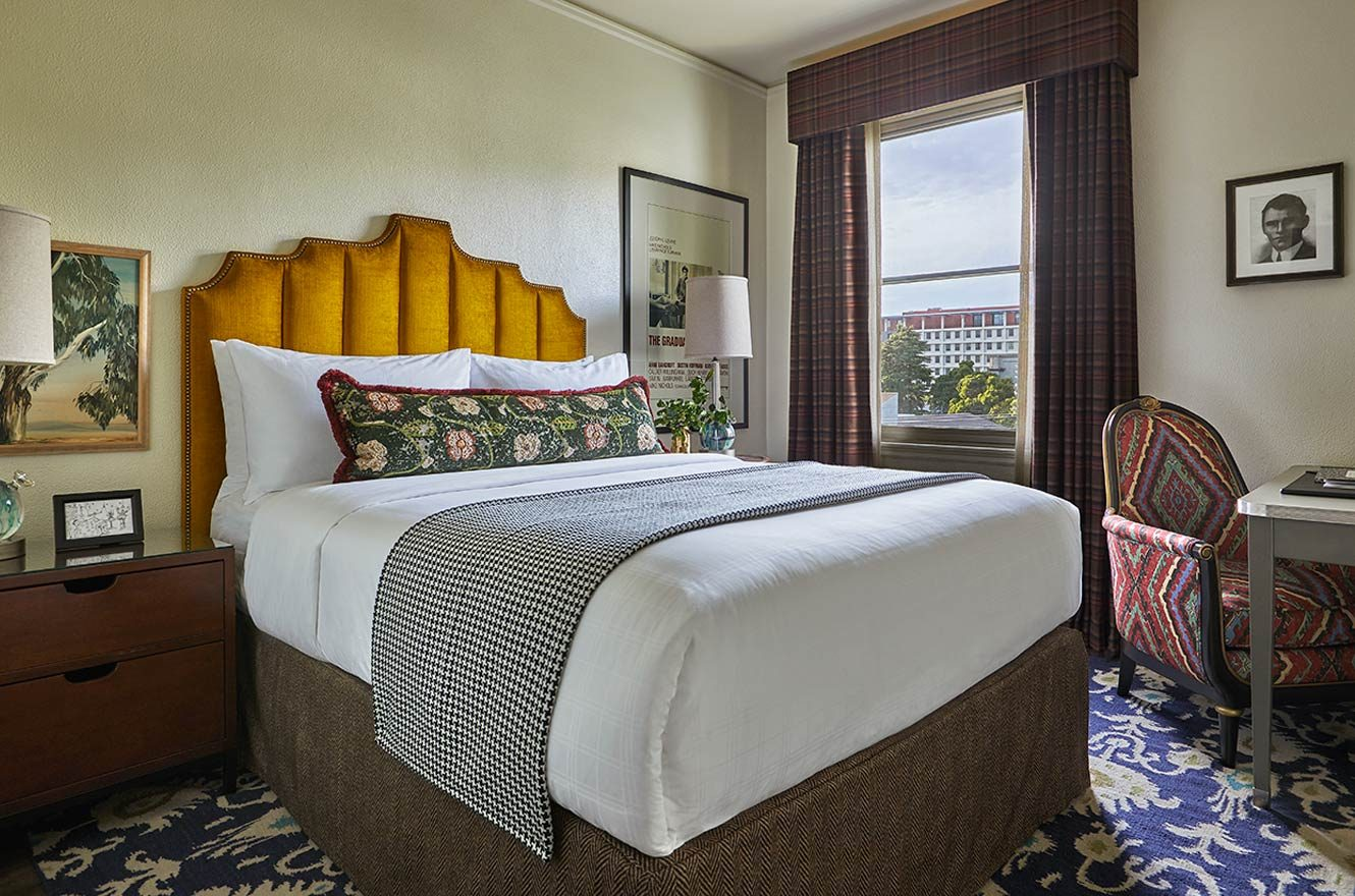 queen bed hotel room with working station
