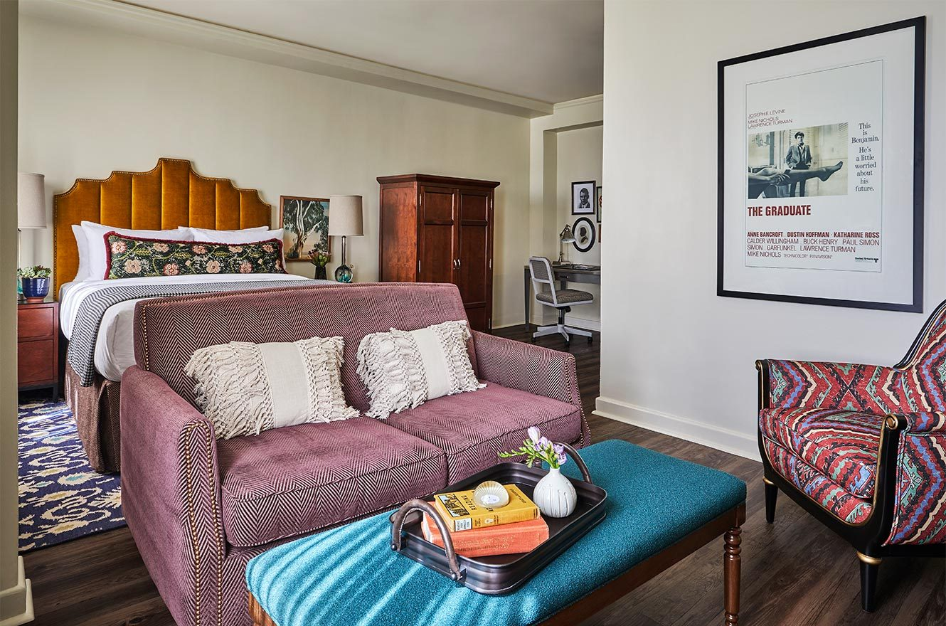 king bed hotel suite with couch and accent chair