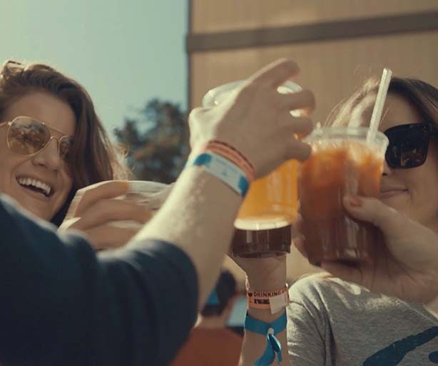 friends toasting drinks at a tailgate