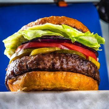 view underneath a burger with lettuce and tomatoes