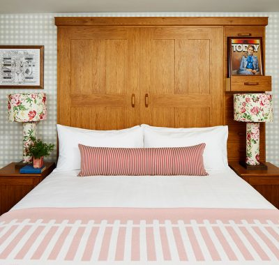 A bed with a wooden head board and floral lamps