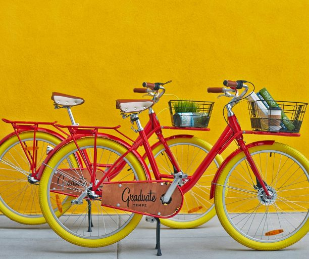 Two red Graduate Bikes against a yellow wall