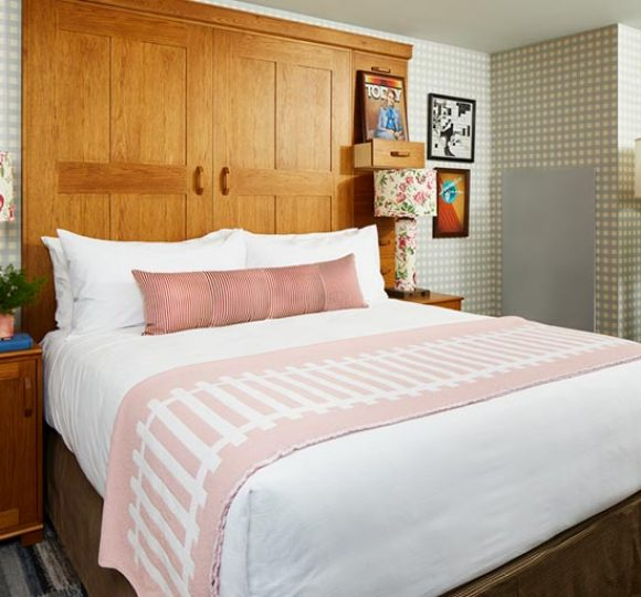 A king bed with a wooden head board and floral lamps