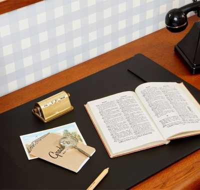 A hotel desk with a book, phone and pencil