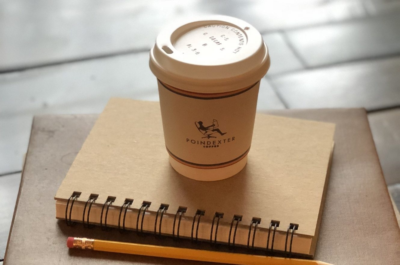 Poindexter Coffee cup resting on a notebook