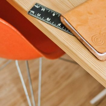 Desk with right angle ruler, notebooks and a copic pen.