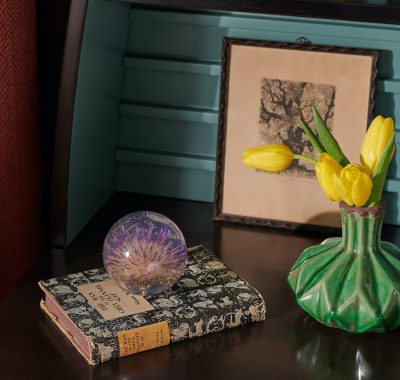 guestroom bedside table with book and vase of yellow flowers