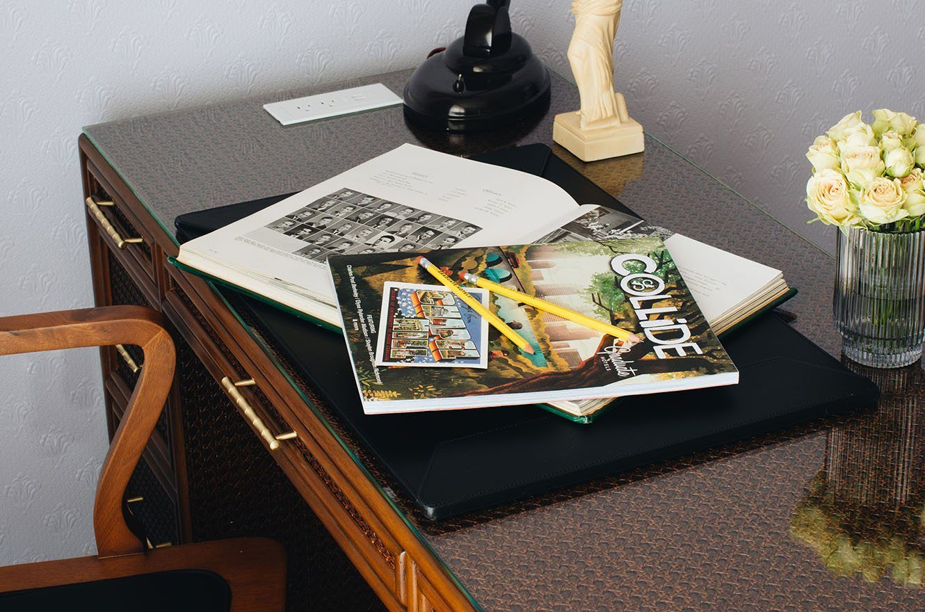 Desk with Graduate Hotels magazine and vase of white flowers