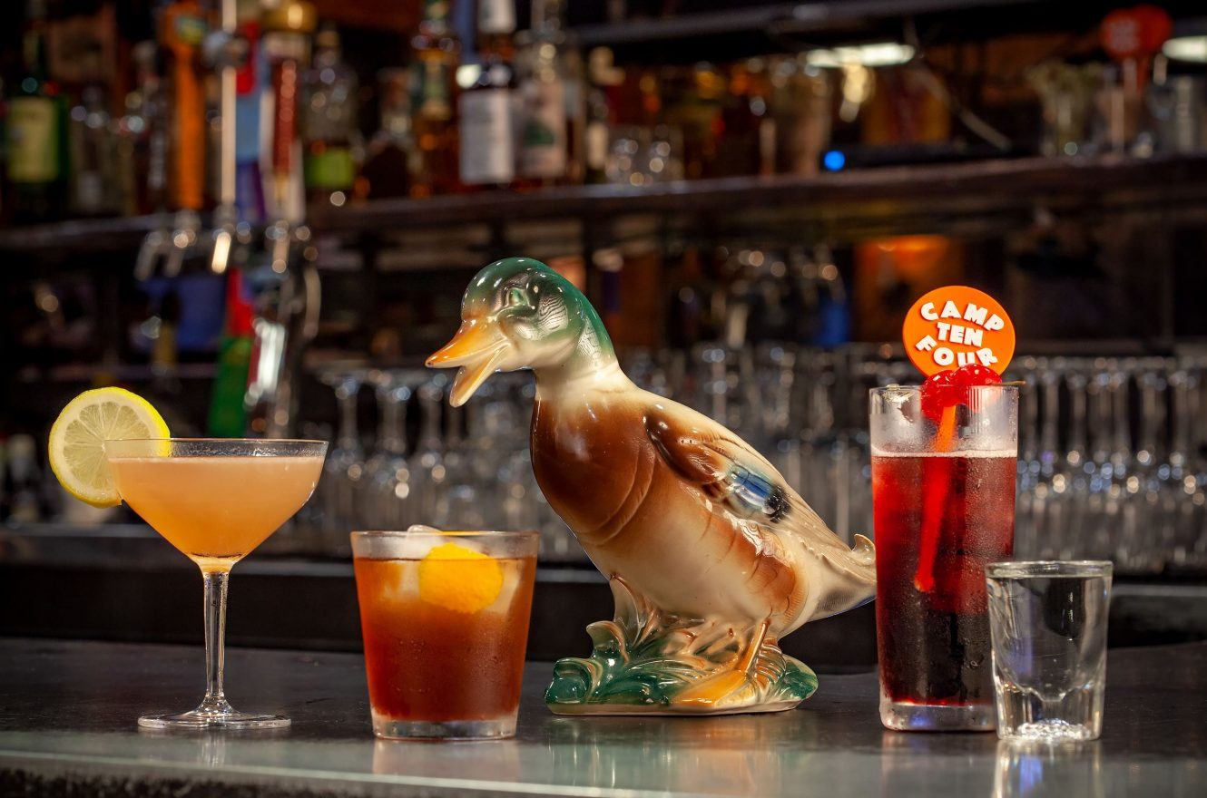 Cocktails and wooden duck on the bar at Camp Ten Four