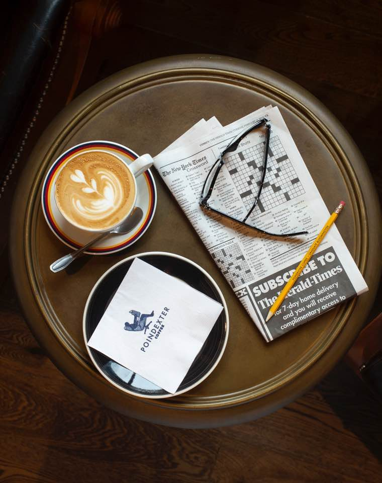 A cappuccino sitting on a table with a crossword puzzle