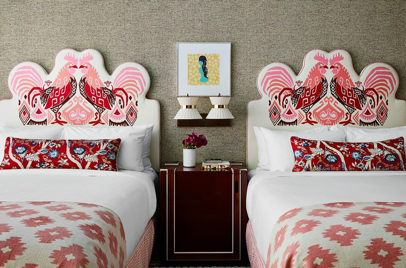 Two queen-sized beds with a bedside table in between