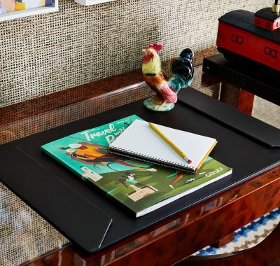 The desk top with a notebook and a Graduate Hotel magazine