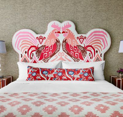 A bed with a rooster-patterned headboard with bedside tables and lamps on either side