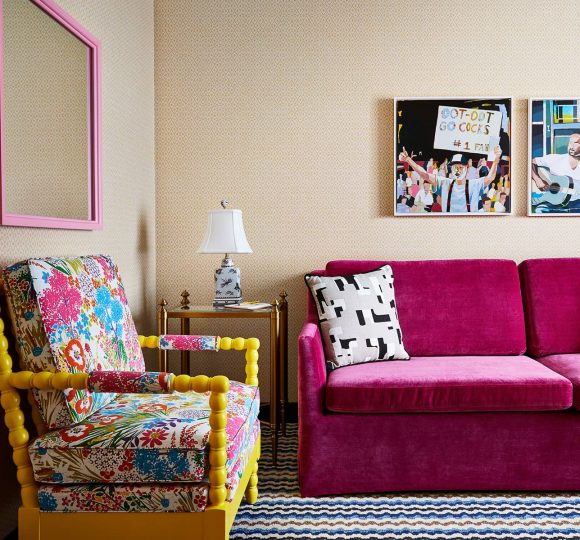 The guest room sitting area with a bright pink couch and a yellow armchair