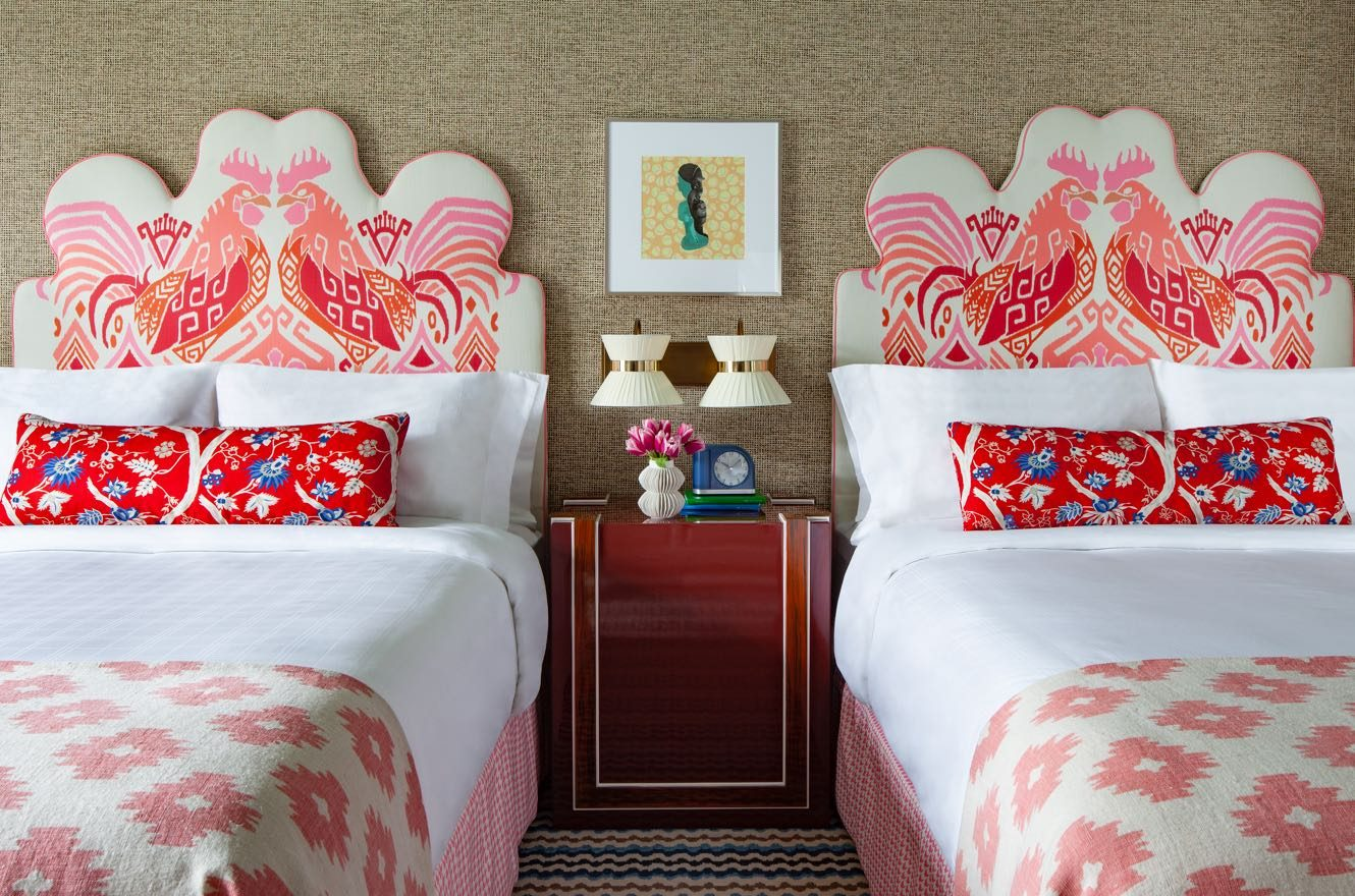 Two Queen beds with white sheets and red accent pillows