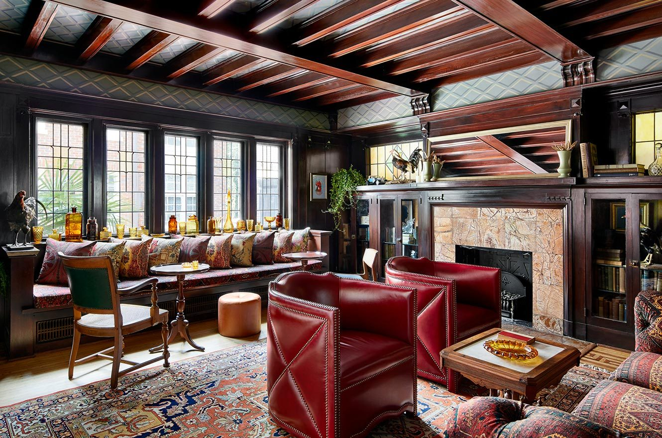 A room with plenty of different seating with wooden beams on the ceiling and a fireplace