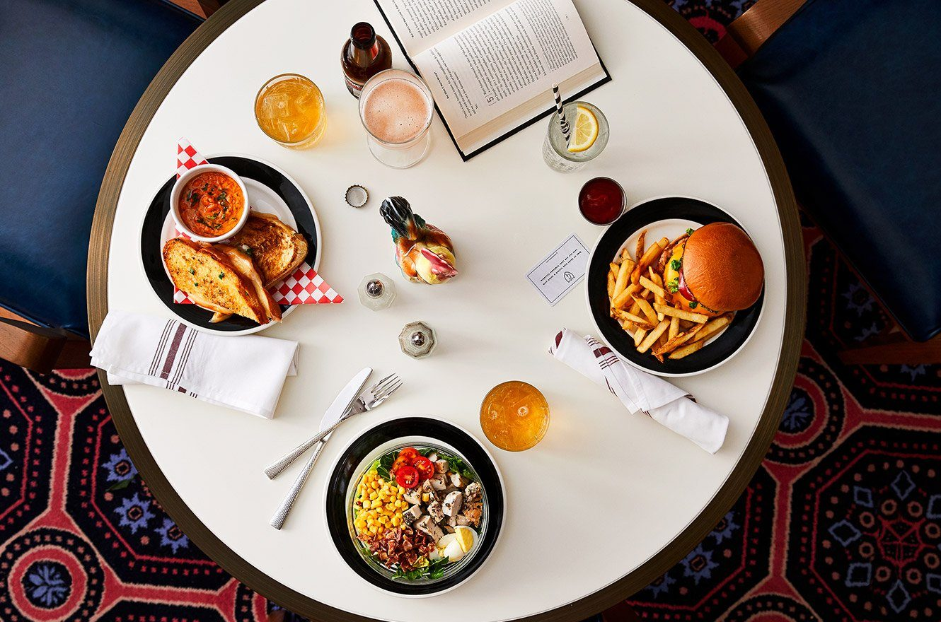 A table with a book, a burger with fries, a grilled cheese sandwich and a chop salad