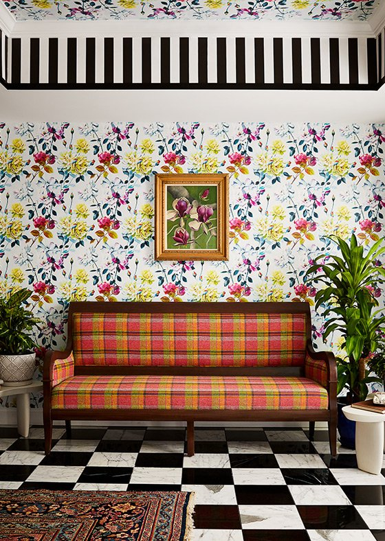 Plaid-patterned couch up against a floral-patterned wallpaper with some plants on either side