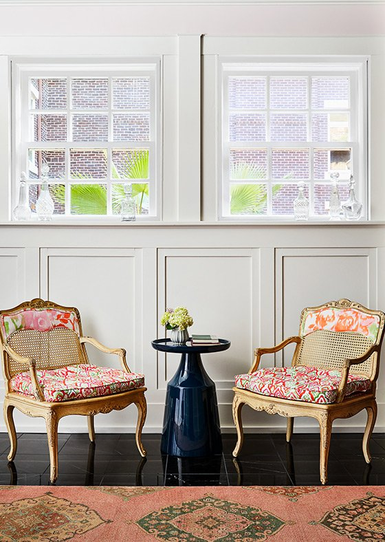 A dark blue side table between two floral-patterned armchairs
