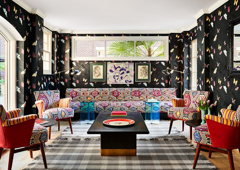 A sitting area in the lobby with butterfly patterned wallpaper