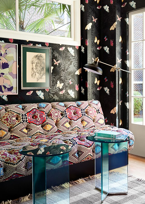 Patterned couch against butterfly-patterned wallpaper