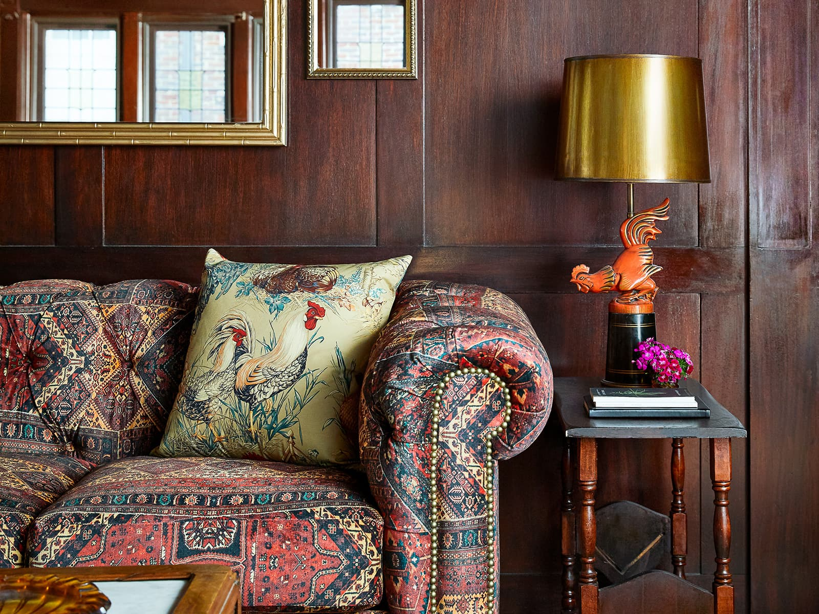Patterned couch with a side table and rooster lamp