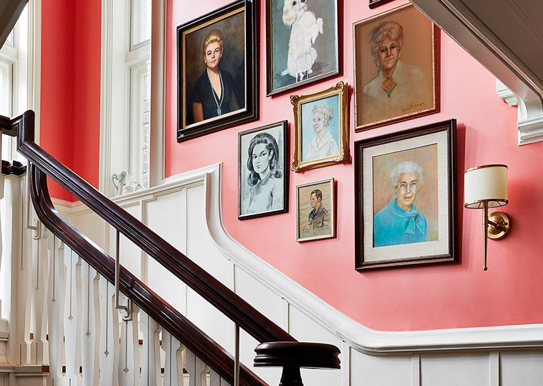 A staircase wall lined with framed paintings