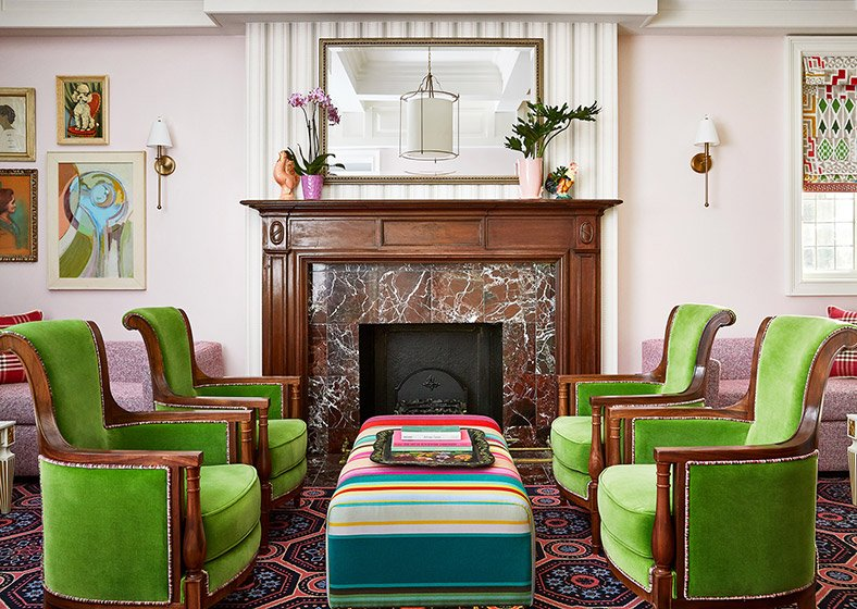 A sitting area in the lobby with bright green armchairs and a marble fireplace