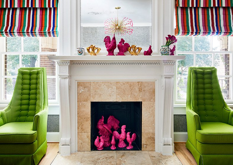 A fireplace with pink chicken figurines and green armchairs on either side
