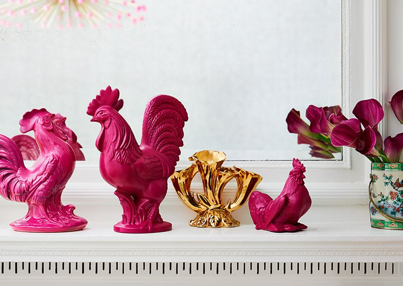 Pink rooster figurines on a fireplace mantel