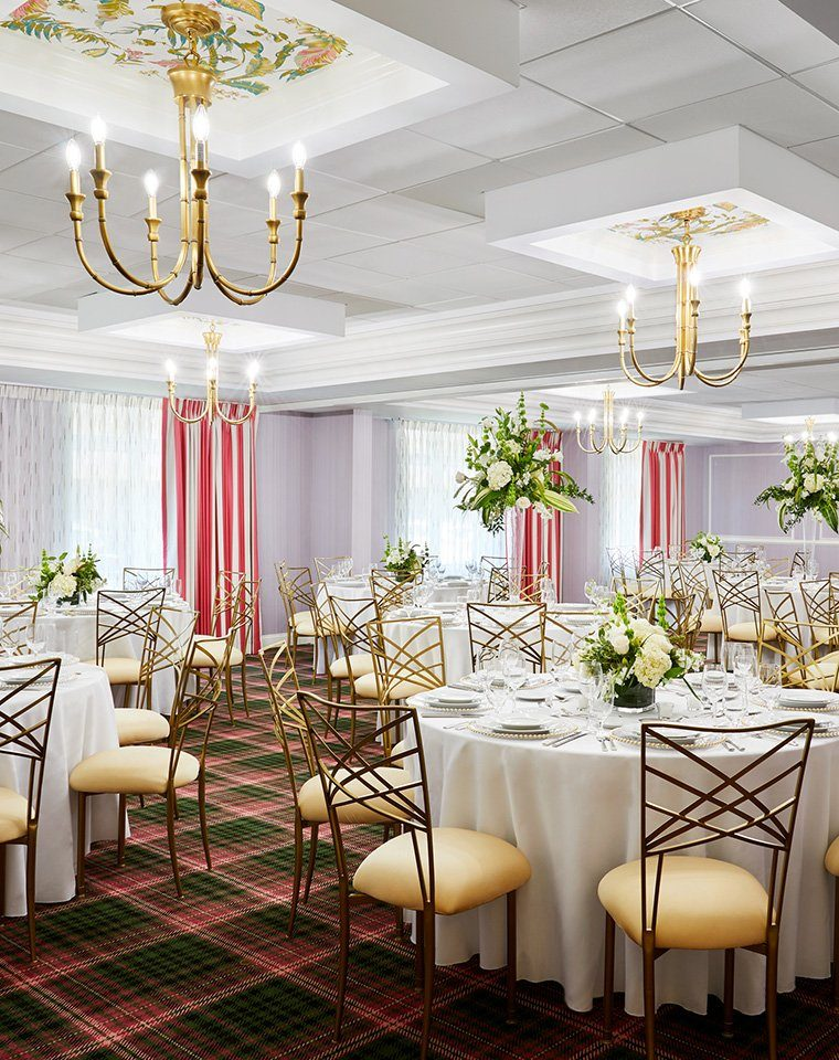 Meeting space with chandeliers and tables set for an event