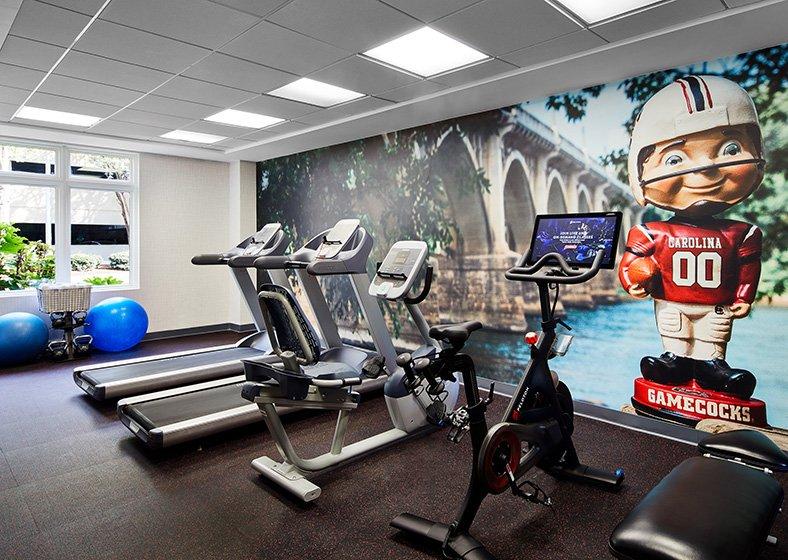 Treadmills, seated elliptical machine and Peloton bike in the hotel gym