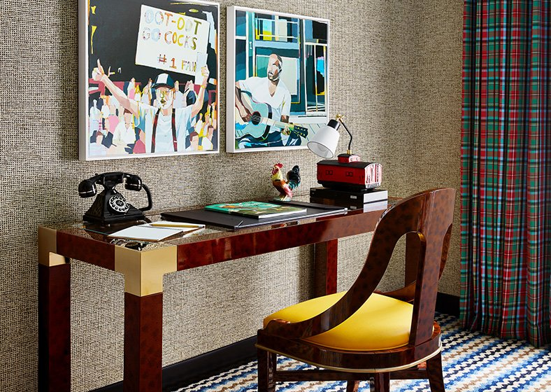 A desk inside the guest room with a vintage telephone and art on the wall