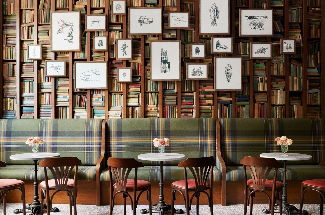 cafe tables in front of a wall of books and art at Graduate East Lansing
