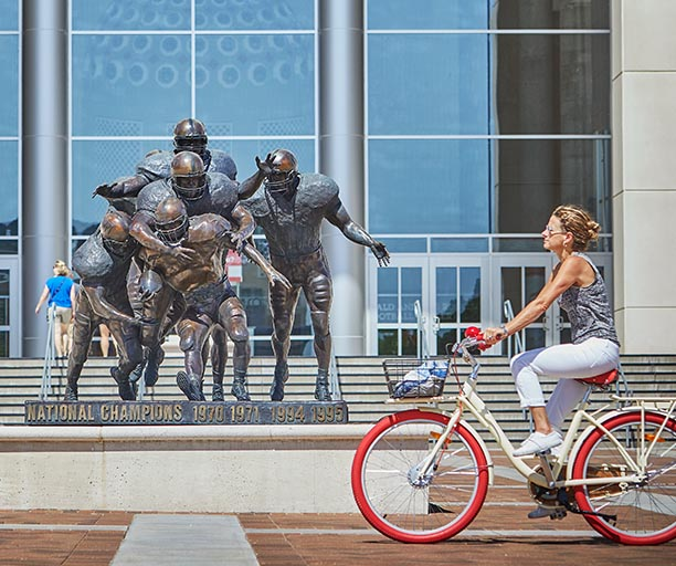woman biking past nebraska football statue