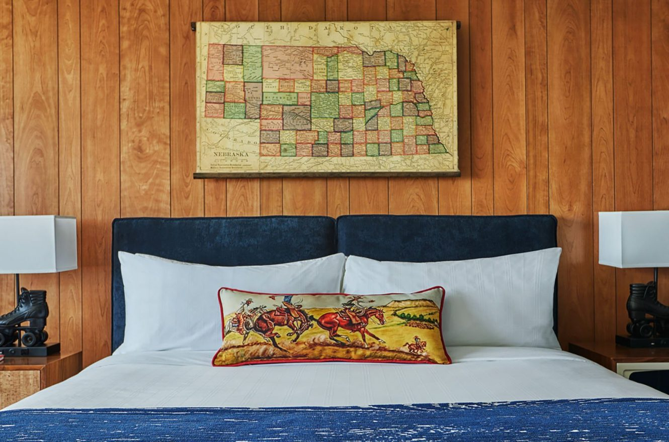 A comfy King bed with a map of Nebraska above the headboard