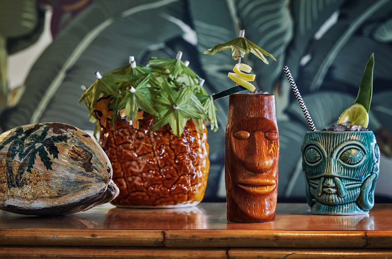 Three different tiki cocktails sitting on a counter