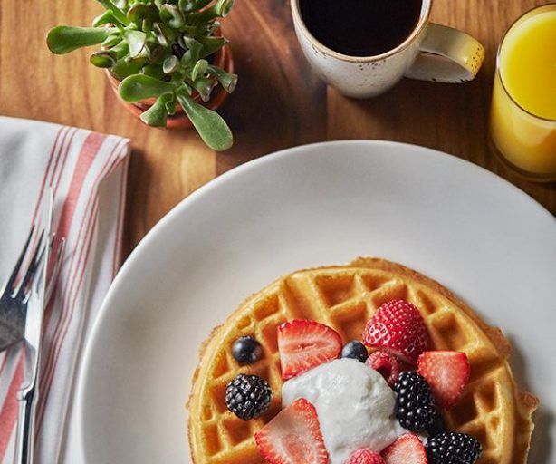 waffle on a plate with strawberries and whip cream on top