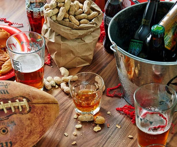 beers on a table with peanuts and a football