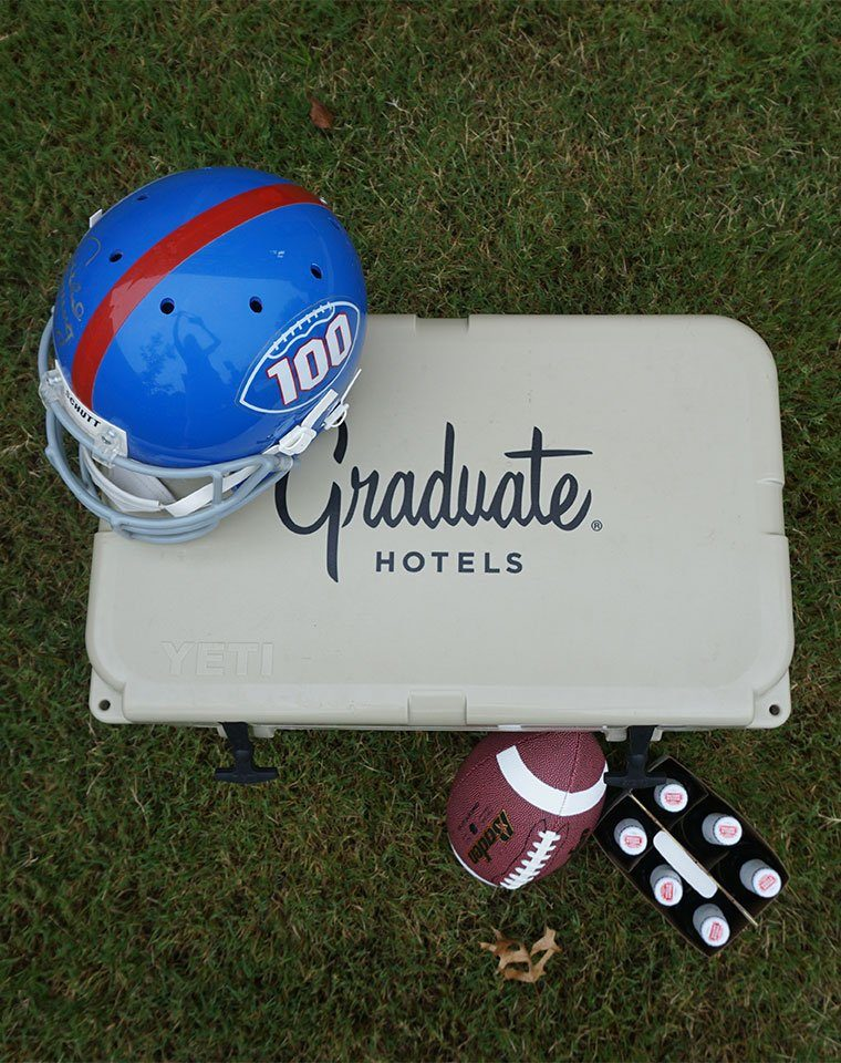 graduate hotels cooler with a football and helmet next to it