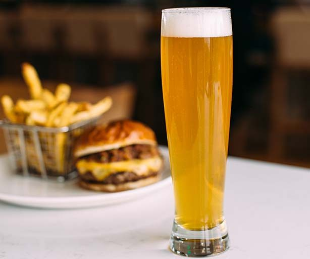 tall glass of beer with a burger in the background
