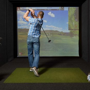 Man playing on a golf simulator