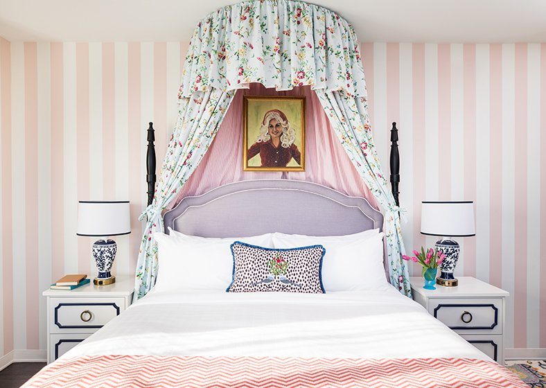 A king bed with a portrait of Dolly Parton above the headboard